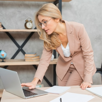 Businesswoman standing at workplace using laptop