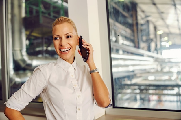 Businesswoman standing in control room in heating plant and having important phone conversation.