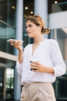 Businesswoman standing in front of office building talking on speaker mobile phone