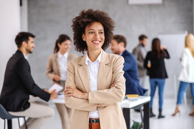 Предприниматель, стоя в зале заседаний со скрещенными руками во время встречи.