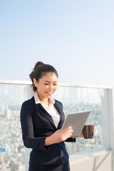 Деловая женщина, стоящая в офисе с электронным блокнотом