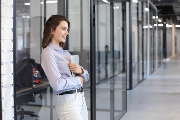 Предприниматель, стоя в коридоре офиса с цифровым планшетом.