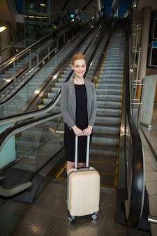 Businesswoman standing near escalator with luggage