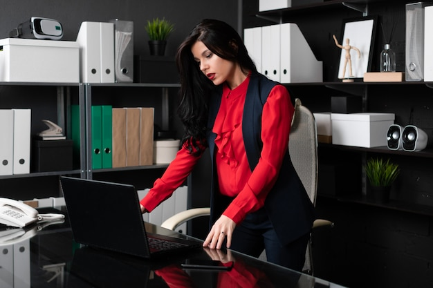 Businesswoman standing near the table and looking at the laptop screen
