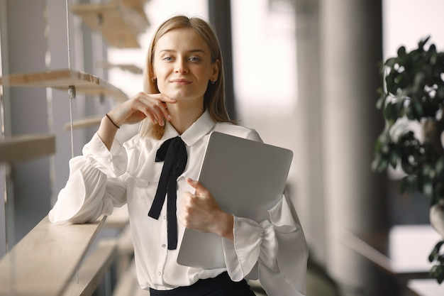 Businesswoman standing in the office with a laptop