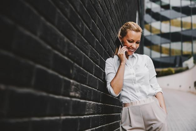屋外に立ってスマートフォンを使用して実業家