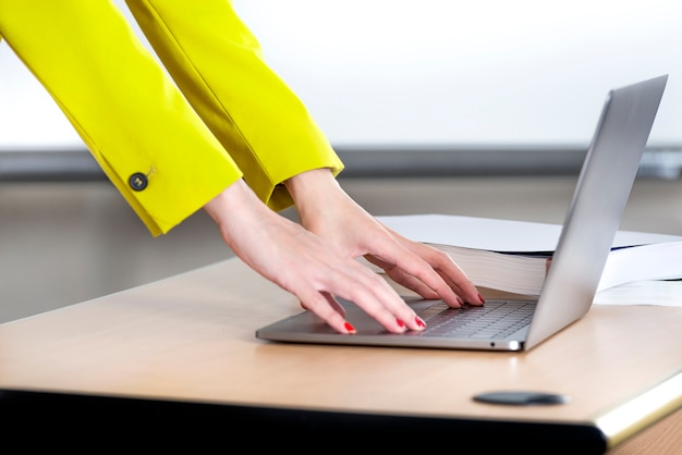 Businesswoman standing while typing on laptop