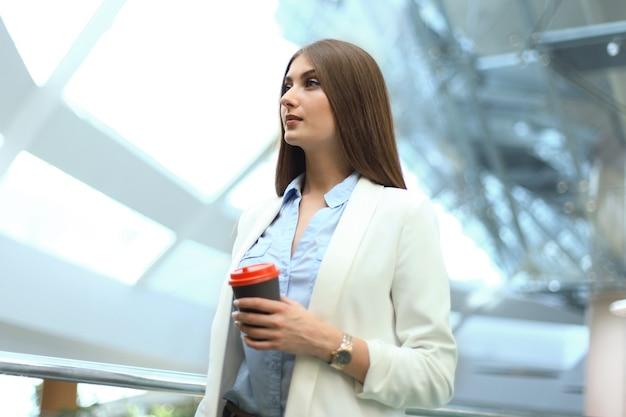 オフィスで紙コップにコーヒーと立っている実業家。