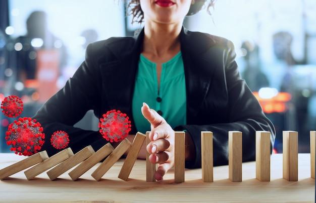 Деловая женщина останавливает падение цепи вирусами, как игра в домино. концепция предотвращения кризисов и сбоев в бизнесе.