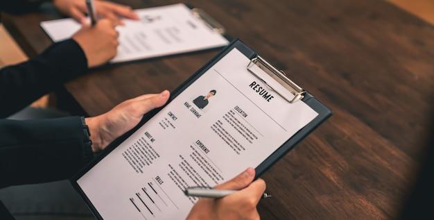 사업가는 이력서 고용주를 제출하여 책상에 있는 입사 지원 정보를 검토하고 회사가 해당 직무에 동의할 수 있는 능력을 제시합니다.