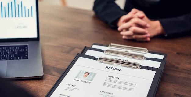 実業家は、机の上の求人応募情報を確認するために履歴書雇用主を提出し、会社が仕事の位置に同意する能力を提示します。