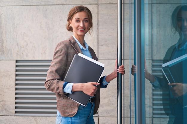 屋外の企業の建物の外観に立っている実業家成功した女性ビジネスパーソン