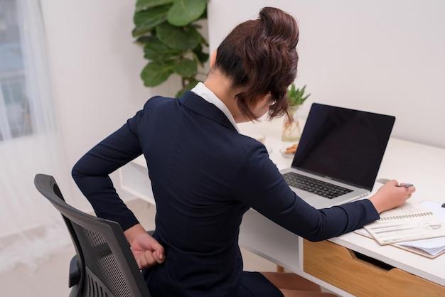 Деловая женщина страдает от боли в спине и пояснице в офисе