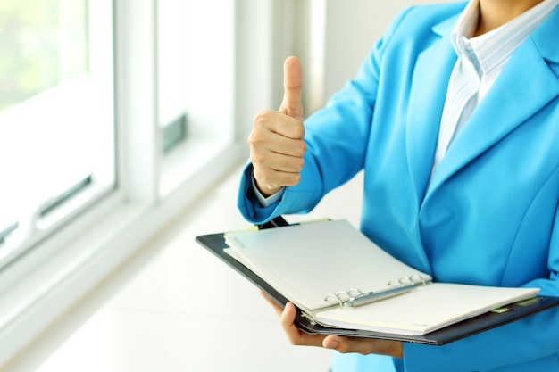 Businesswoman in suit lifts his hand make the superb sign