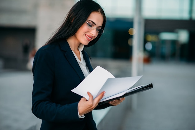 Businesswoman in suit works with notebook outdoor, business center. modern financial building, cityscape.