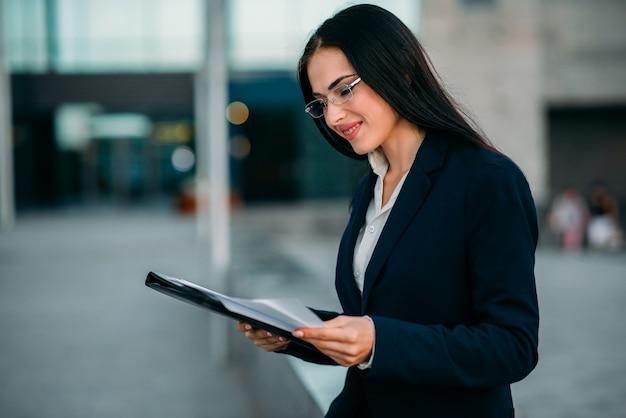 Businesswoman in suit writing in notebook outdoor