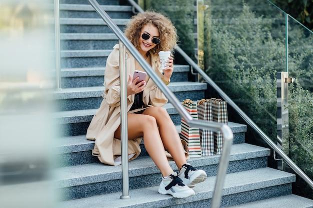 La donna d'affari con gli occhiali da sole tiene in mano le borse della spesa e il telefono sorridendo dopo aver camminato per la strada.