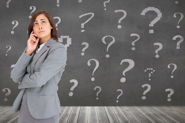 A businesswoman surrounded by question marks