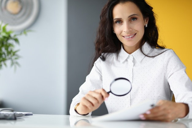 Businesswoman at table in office smiles and holds magnifying glass