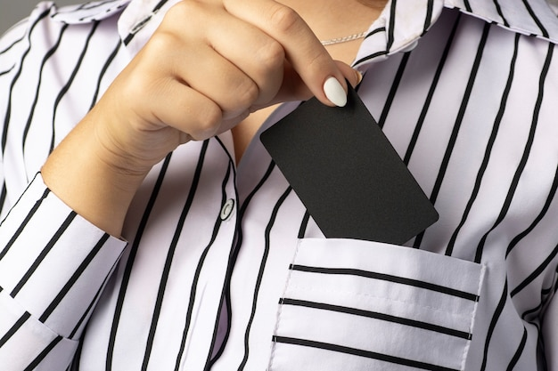 Businesswoman takes a black business card out of her blouse pocket.