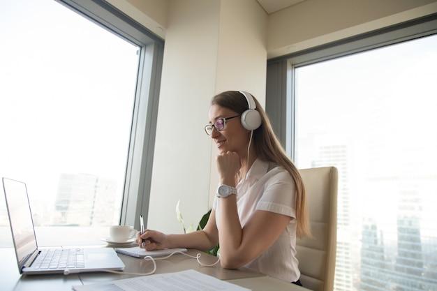 La donna di affari partecipa alla riunione in linea
