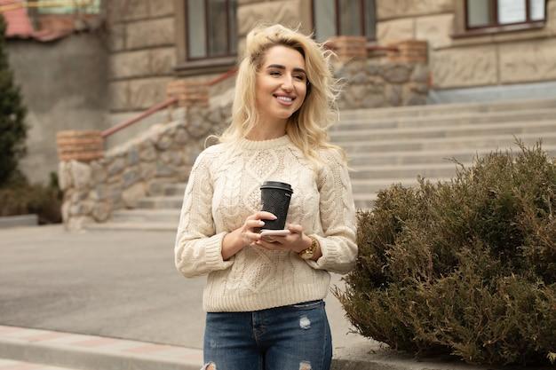 Предприниматель, принимая перерыв на кофе и с помощью смартфона