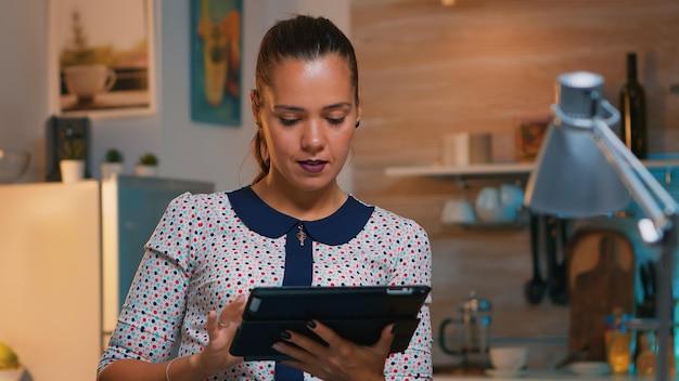 Imprenditrice prendendo pausa utilizzando tablet a tarda notte seduto in cucina moderna. impiegato impegnato e concentrato che utilizza la moderna tecnologia di rete wireless facendo gli straordinari, scrivendo, cercando.