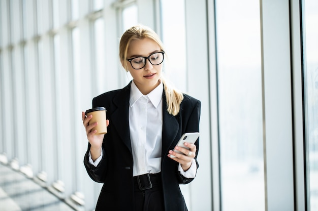 Businesswoman taking a coffee break and using smartphone in office