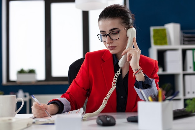 Businesswoman taking notes on clipboard sitting at desk in corporate office while taking