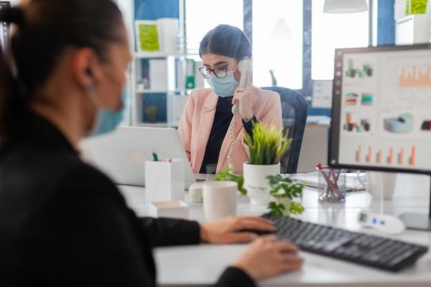 여성 사업가는 전화로 대화하는 동안 노트북으로 메모를 하고, 쉴드 뒤에 있는 새로운 일반 사무실에서 코로나바이러스 발병 동안 사회적 거리를 유지하는 얼굴 마스크를 쓰고 있습니다.