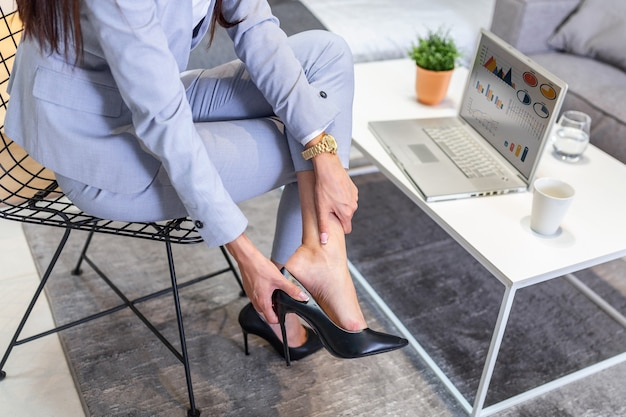 Businesswoman taking off high heels shoes after work at home.