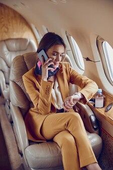 Деловая женщина разговаривает по мобильному телефону и смотрит время на наручных часах в частном самолете. современный пассажирский самолет. молодая европейская женщина носит официальный костюм. гражданская авиация. концепция авиаперелетов и бизнеса