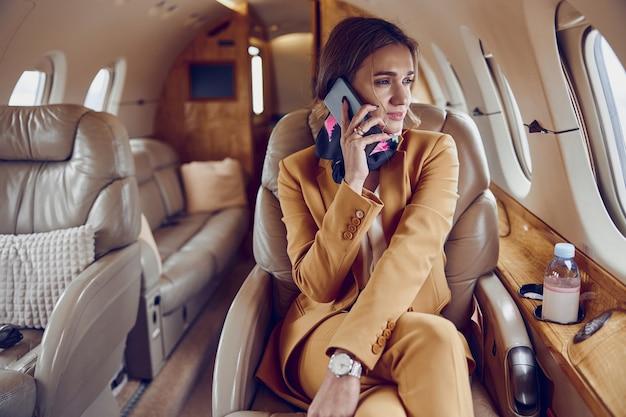 実業家はプライベート飛行機のジェット機で携帯電話で話します。現代の旅客機。若い白人女性はフォーマルなスーツを着て、窓から見ています。民間航空。空の旅とビジネスの概念