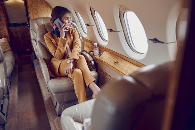 実業家はプライベート飛行機のジェット機で携帯電話で話します。現代の旅客機。若いヨーロッパの女性はフォーマルなスーツを着て、窓から見ています。民間航空。空の旅とビジネスの概念