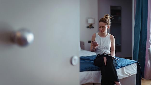 Коммерсантка говоря на телефоне и работая с таблеткой в гостиничном номере.