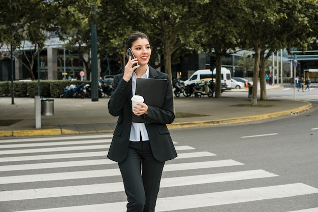 Businesswoman talking on cell phone crossing the road