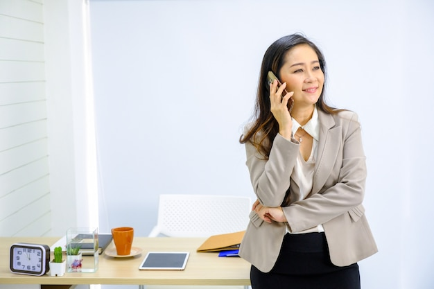 Businesswoman talking on mobile phone while standing by window in office.