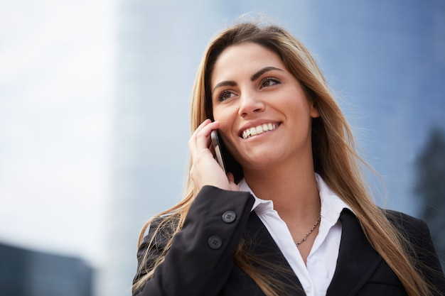 Businesswoman talking to mobile in urban environment