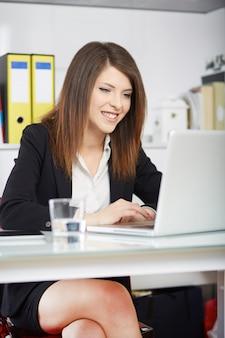 Businesswoman talking to mobile and working in office with laptop