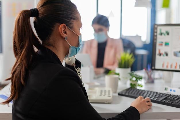 Деловая женщина разговаривает по стационарному телефону в новом обычном офисе во время глобальной пандемии коронавирусного гриппа, носит маску в качестве меры безопасности, сохраняя социальное дистанцирование.