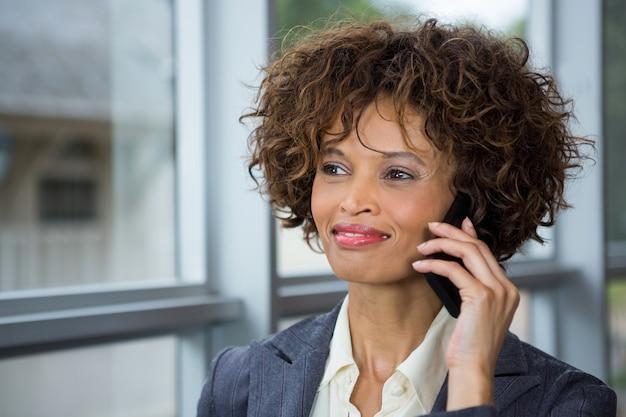 Деловая женщина разговаривает по мобильному телефону в конференц-центре