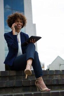 オフィスビルの近くで携帯電話で話している実業家