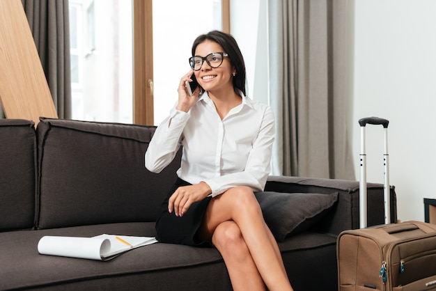 ソファに座りながら携帯電話で話している実業家