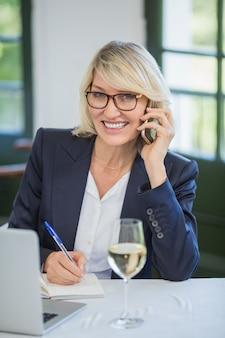 日記に書きながら携帯電話で話している実業家