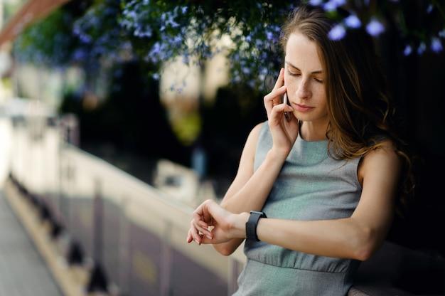 スマートフォンで話している実業家と路上でスマートウォッチをチェック