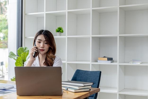 Деловая женщина разговаривает по телефону со своим деловым партнером, она сидит в отдельной комнате, в комнате, украшенной растениями, и книжными полками на столе с рабочими бумагами и ноутбуком. концепция азиатских женщин.