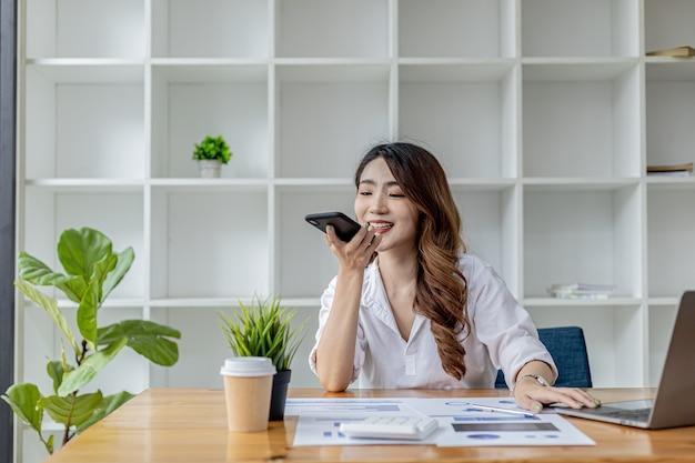 비즈니스 파트너와 전화 통화를 하는 사업가인 그녀는 책상 위의 식물과 책꽂이로 장식된 방에 업무용 서류와 노트북이 있는 개인실에 앉아 있습니다. 아시아 여성 개념입니다.
