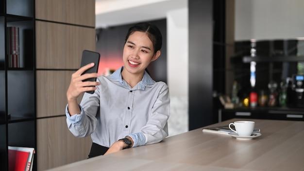 Деловая женщина разговаривает по видеозвонку на смартфоне со своими друзьями в офисе.