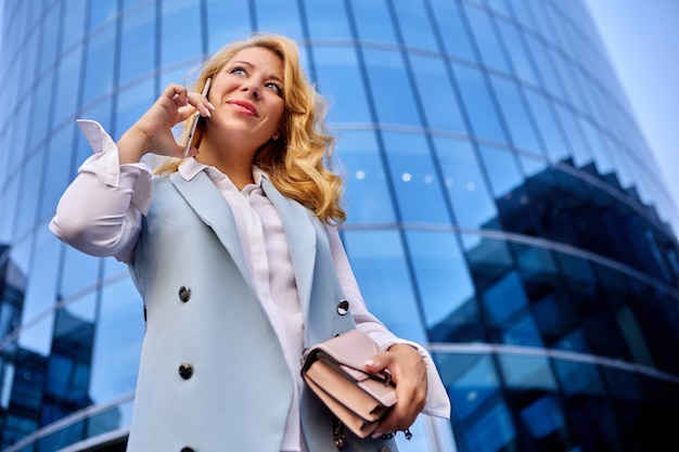Businesswoman talking on phone in front of office building or business center