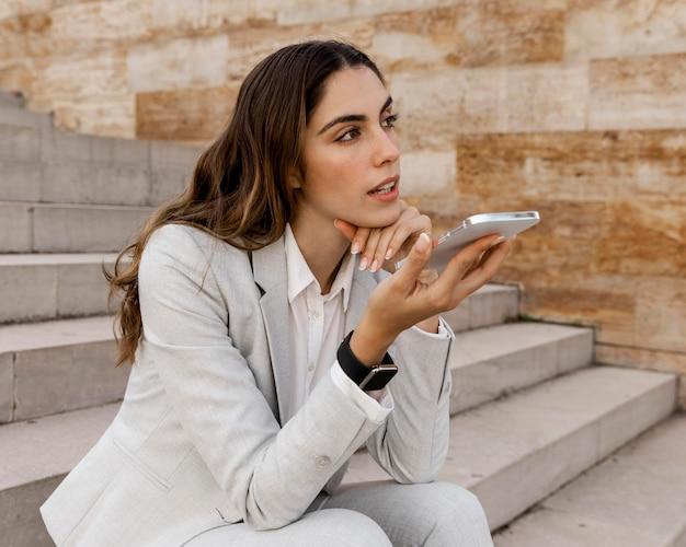 Imprenditrice parlando al telefono mentre è seduto all'aperto